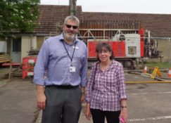 Russ Fowler Director of Financial Reporting & resident Mrs Wilson in front of drilling rig